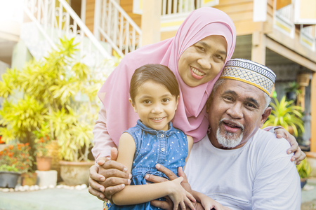 Photo pour Girl with her grandparents in front of wooden house - image libre de droit