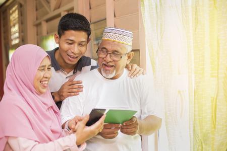 Foto de Family with an Eid greeting card and smartphone - Imagen libre de derechos
