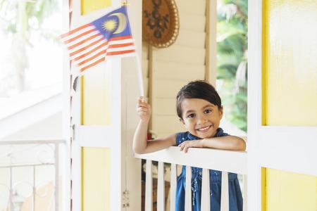 Photo pour Malaysian girl waving national flags - image libre de droit