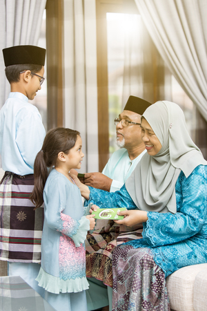 Photo for Muslim kids receiving green envelope from grandparents during Eid al-Fitr - Royalty Free Image