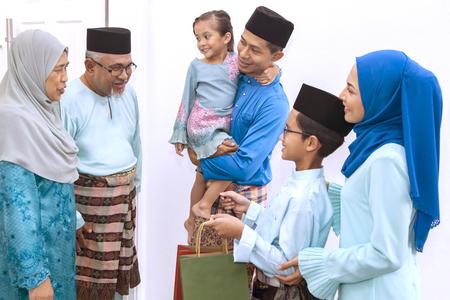 Foto de Muslim family visiting senior couple on Eid al-Fitr - Imagen libre de derechos