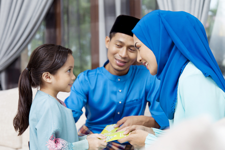 Photo for Muslim girl receiving green envelopes from parents during Eid al-Fitr - Royalty Free Image