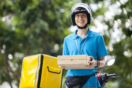Photo pour Delivery man carrying boxes of food - image libre de droit