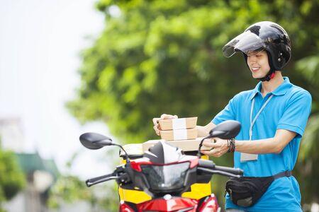 Photo pour Food delivery man taking food from a bag - image libre de droit