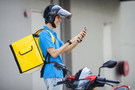 Photo pour Food delivery man checking location with a mobile phone - image libre de droit