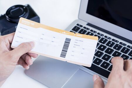 Photo pour Man with boarding pass doing an online check in - image libre de droit