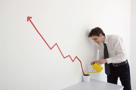 Man watering pot of line graph encouraging business growth