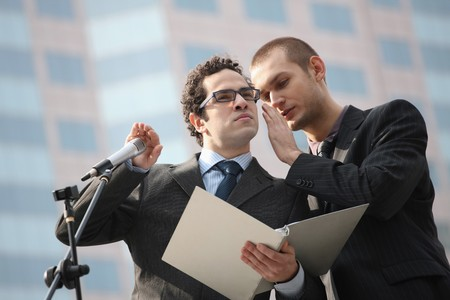 Man whispering into businessman's ear, businessman covering the microphone while listening