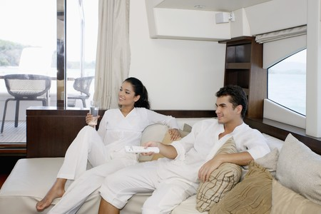 Couple watching television in yacht living room