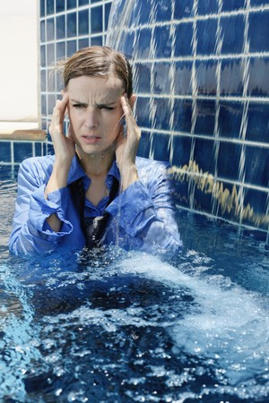 Businesswoman with headache standing in swimming pool