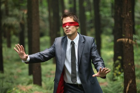 Businessman with blindfold walking aimlessly in the forest