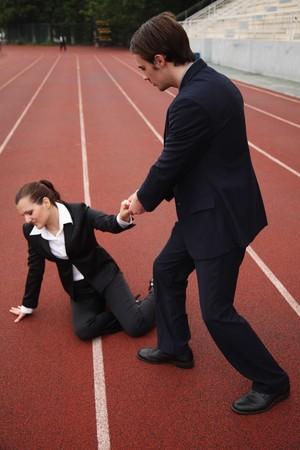 Businessman helping fallen businesswoman