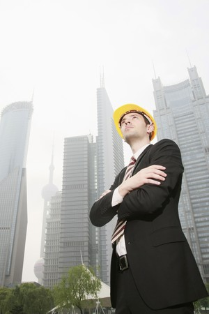 Businessman wearing safety hat with arms crossed