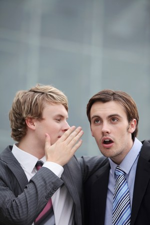 Businessman whispering into his colleague's ear