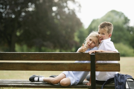 Photo for Boy and girl sitting on bench - Royalty Free Image