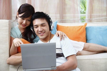 Photo for Man and woman using laptop, man with headphones - Royalty Free Image