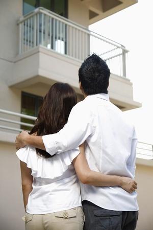 Foto de Man and woman embracing, looking at their new home - Imagen libre de derechos