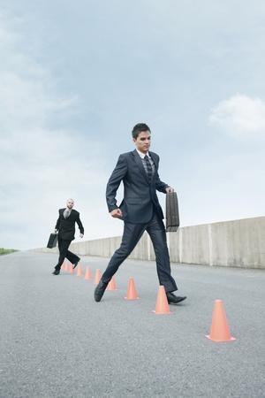 Businessmen running in between traffic cones