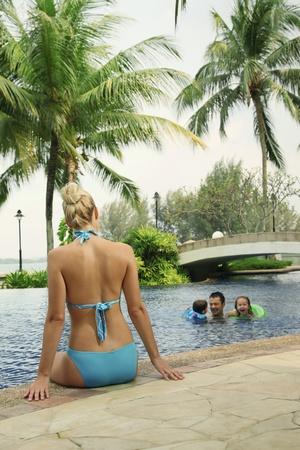 Woman in bikini sitting at the edge of pool watching her family swim