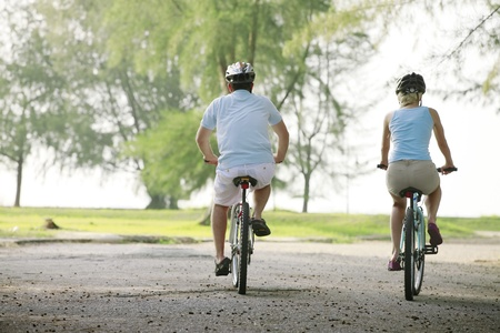 Photo for Man and woman cycling in the park - Royalty Free Image