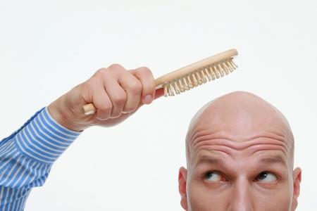Bald man combing his head
