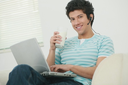 Man using laptop while holding a glass of milk