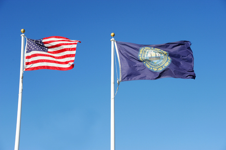 New Hampshire state flag and USA national flag waving under blue sky