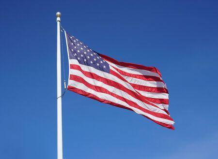 Photo pour waving USA flag on pole against blue sky - image libre de droit