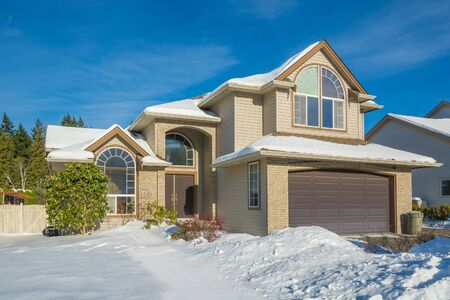 Foto de Big luxury house with front yard in snow. Residential house on winter sunny day - Imagen libre de derechos
