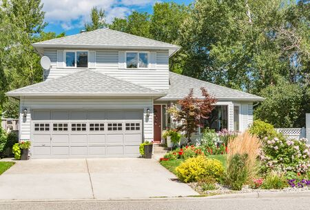 Photo for A perfect neighbourhood. Family house with landscaped front yard on bright sunny day in British Columbia - Royalty Free Image