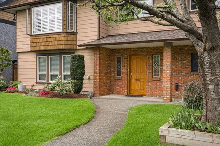Photo pour Nice main entrance of old family house with brick textured wall and concrete pathway over front yard lawn - image libre de droit