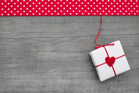 Gift or present with red hearts for mother s day, valentine s day, christmas or birthday on a wooden background for a greeting card