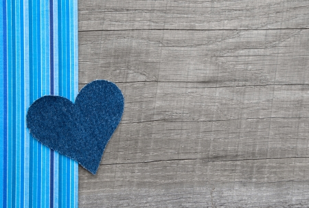 Denim blue heart on wooden background in country style
