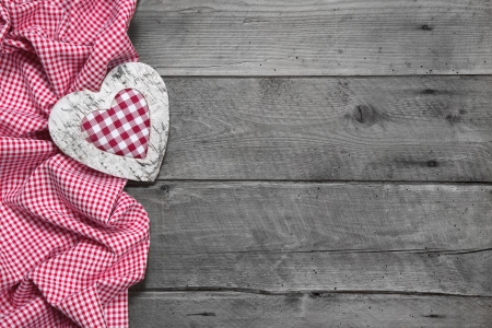 Wooden background for a greeting card or a voucher with a red chequered heart for christmas
