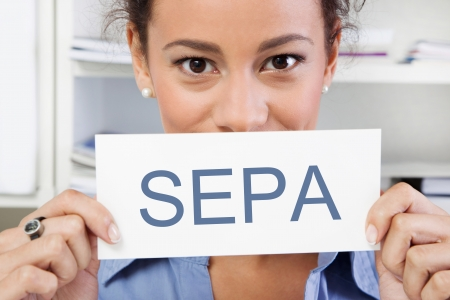 Young woman looking at camera holding a SEPA sign isolated on white