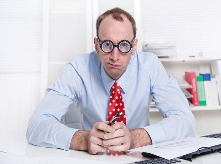 Angry or frustrated young businessman sitting thoughtful at desk and broods about a solution - lost responsability.