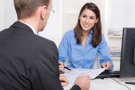 Photo pour Saleswoman: Businesswoman sales an insurance or makes finance at desk - supporting a customer. - image libre de droit