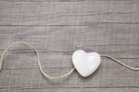 Wooden background with a white heart for wedding or valentines day.