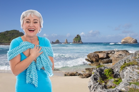 Older woman on holiday on the sea - blue ocean
