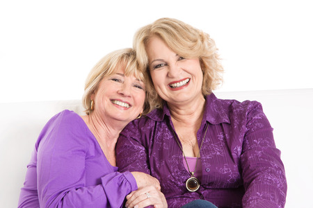 Portrait of two older women smiling in purple or violet shirts