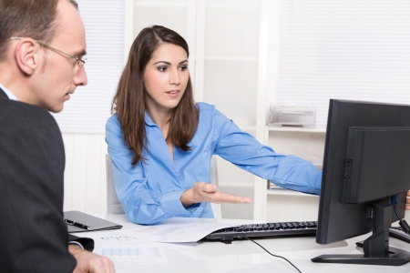 Photo pour Two business people talking together at desk - adviser and customer or recruitment - image libre de droit
