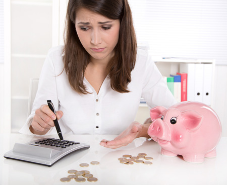 Woman is counting her money - sitting sad at desk and has lost her dreams