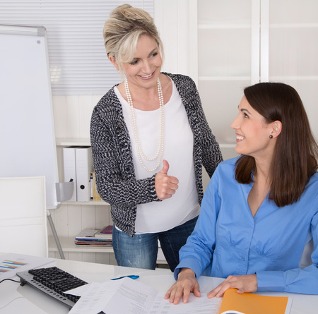 Senior female manager praise her young assistantt in the office.