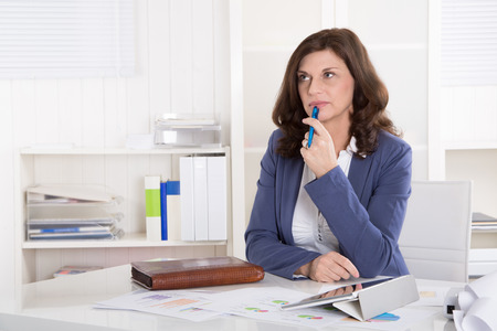 Portrait: Unhappy older pensive business woman sitting at desk.