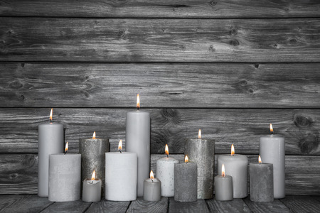 Burning candles in white and grey on wooden shabby chic background.Idea for a card for mourning, death or christmas.
