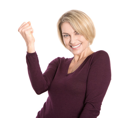 Isolated successful and happy older woman in pullover making fist gesture の写真素材
