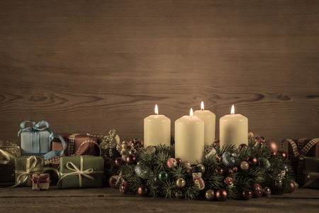 Advent wreath or crown with four burning candles and christmas gifts for a voucher.