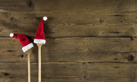 Photo for Funny wooden christmas background for a menu card with wooden spoon and two red santa hats. - Royalty Free Image