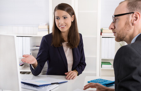 Customer and smiling female financial agent in a discussion at desk.