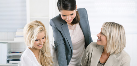 Successful team of smiling businesswoman sitting at desk wearing business outfit.